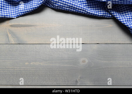 a checked gingham picnic tablecloth on old wooden table top view - Stock Photo