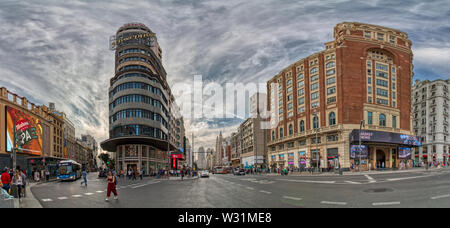 Madrid, Spain - June 20, 2019: Panoramic view with a dramatic sky, of Gran Vía de Madrid - Stock Photo