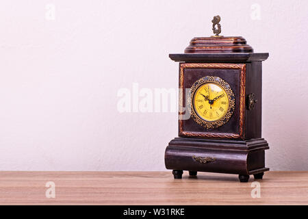 Antique Victorian clock on a wooden table. - Stock Photo