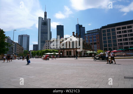 Frankfurt, Germany - July 06, 2019: Pedestrians and visitors strolling through the city on the Hauptwache with tower blocks of the financial district - Stock Photo