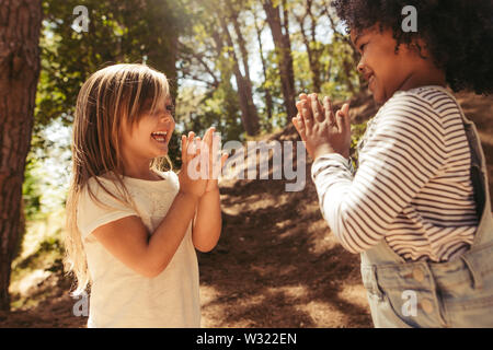Cute girls playing clapping games outdoors. Children playing games in forest. - Stock Photo