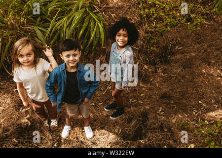 Three kids standing together in forest and looking at camera. Multi-ethnic children playing in woods.