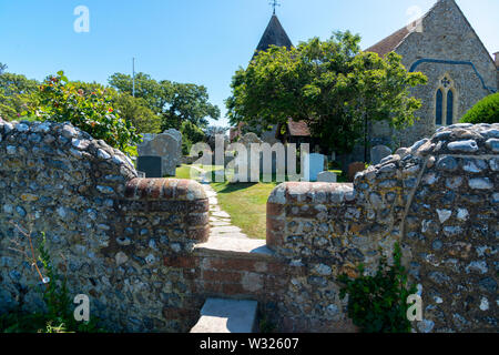 Public footpath passing through the churchyard of the Norman church of St Peter and St Paul in West Wittering, Nr.Chichester, West Sussex, England, UK - Stock Photo