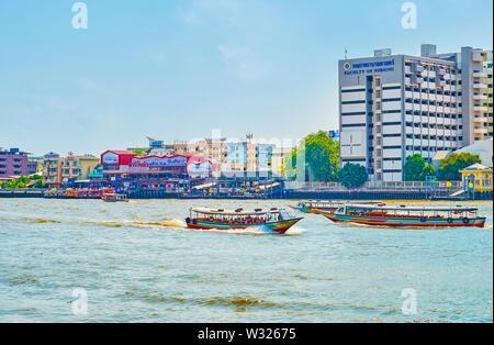 BANGKOK, THAILAND - APRIL 22, 2019: The traditional wooden boats sail along Chao Phraya river and showing tourists main landmarks of the Bangkok's riv - Stock Photo