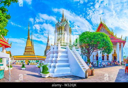 BANGKOK, THAILAND - APRIL 22, 2019: The large courtyard of Wat Pho temple with numerous shrines, pagodas and small belfry in the middle, on April 22 i - Stock Photo