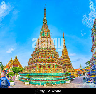 BANGKOK, THAILAND - APRIL 22, 2019: The unique styled pagodas of Phra Maha Chedi in Wat Pho with colorful decorations with chinese glazed tiles, on Ap - Stock Photo