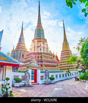 The scenic view on high pagodas of Phra Maha Chedi shrine, one of the most famous part of Wat Pho complex, Bangkok, Thailand - Stock Photo