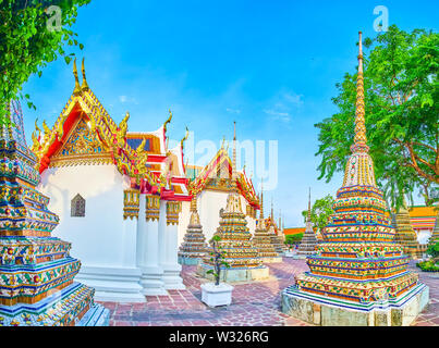 The architecture of Wat Pho religion complex boasts splendid tiled decoration of numerous pagodas and carved gilden patterns of the roofs of Viharns s - Stock Photo