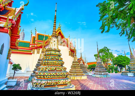 Walk in courtyard of Wat Pho complex along shady alleys and enjoy magnificent decoration of surrounding pagodas is the best way to spend the evening t - Stock Photo