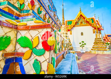 Pagodas of Wat Pho complex richly decorated with glazed colorful tiles in floral patterns, Bangkok, Thailand - Stock Photo