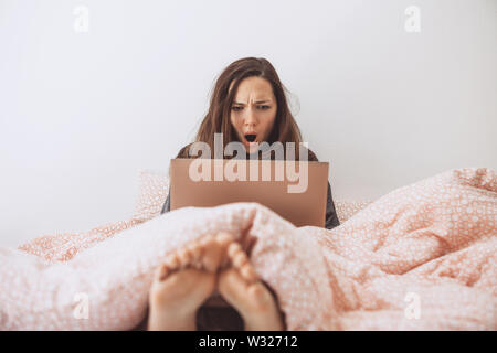 The girl uses the computer in bed. She saw something and was surprised or shocked. - Stock Photo