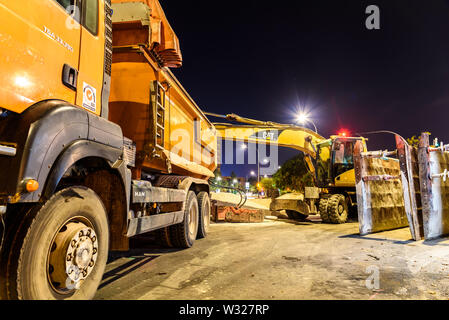 Valencia, Spain - July 4, 2019: A truck next to an excavator parked at night in a sanitation project in a city. - Stock Photo
