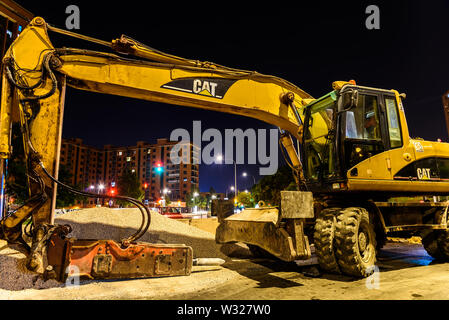 Valencia, Spain - July 4, 2019: An excavator with a pneumatic hammer to break the asphalt in a pipe renovation project in the city, without working. - Stock Photo