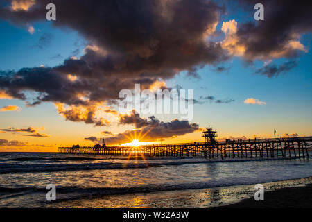 Watching the Sunset through the san clemente pier down at the beach on the sand - Stock Photo