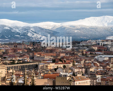 A rooftop view of Segovia, Spain with the snowy mountains in the background taken from the top of the city's cathedral. - Stock Photo