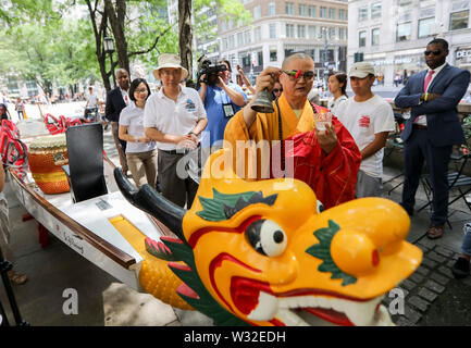 New York, USA. 11th July, 2019. A monk gives blessings during the dragon boat awakening ceremony of the 29th Hong Kong Dragon Boat Festival in New York, the United States, July 11, 2019. A dragon boat awakening ceremony was held in New York's Bryant Park on Thursday as a prelude to the 29th Hong Kong Dragon Boat Festival to be held in August. Credit: Wang Ying/Xinhua/Alamy Live News - Stock Photo