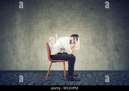 Depressed man upset with bad luck sitting on a chair alone looking down against gray wall background