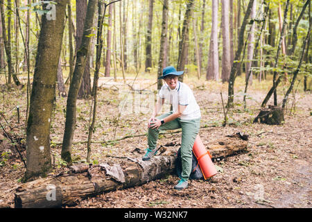 Young woman having trouble feeling knee pain during travel in forest. Injury on way to camp. female tourist got leg injury in forest and gets hurt - Stock Photo