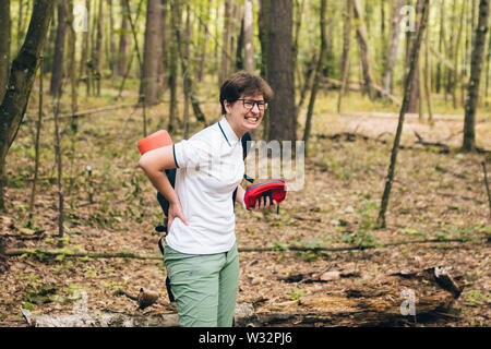 Woman tourist got back injury in forest and gets hurt. Health problem in the journey. Theme Insurance company. Pain in the spine with an active - Stock Photo