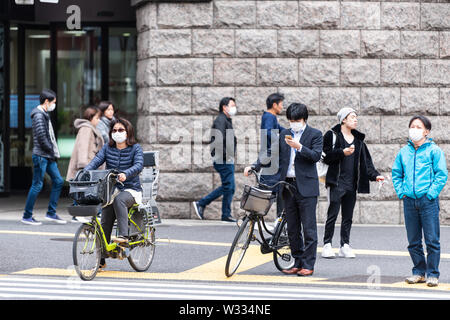 Tokyo, Japan - April 1, 2019: Shinjuku street sidewalk with people waiting to cross road pavement by station building during day - Stock Photo