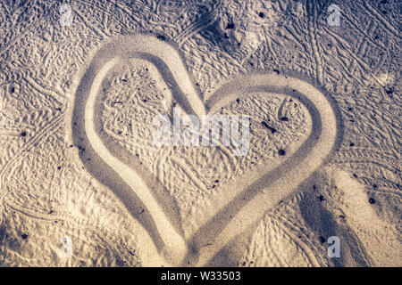 This unique image shows a heart painted in the fine sand of an island in the Maldives - Stock Photo