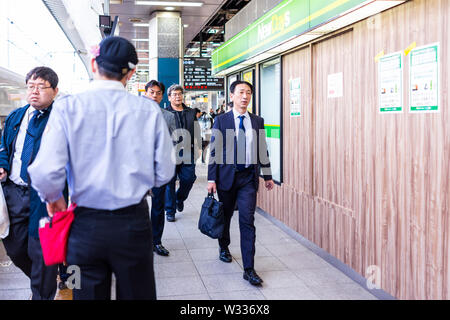 Tokyo, Japan - April 4, 2019: Japanese conductor on platform of Shinjuku JR railway station by bullet train or shinkansen with business people busines - Stock Photo