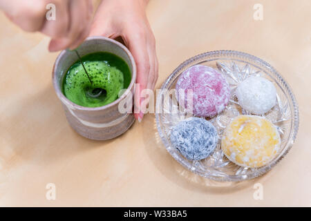 Woman stirring green matcha tea with frother by mochi rice cake Japanese dessert wagashi on wooden table - Stock Photo