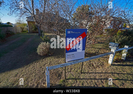 sold sticker across a sold sign outside a house in the northern new south wales town of Glen Innes, australia - Stock Photo