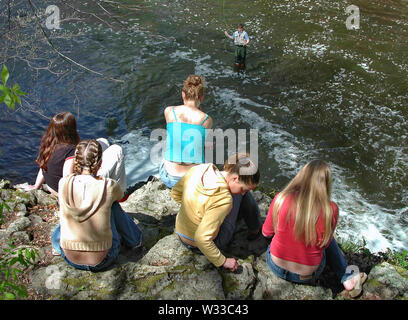 Middlefield, CT USA. May 2016. Young women thinking and sitting on a cliff looking down watching a fisherman in action. - Stock Photo
