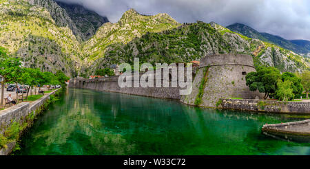Kotor, Montenegro - May 30, 2019: Panorama of Kotor Bay or Boka Kotorska emerald water, mountains, ancient stone city wall of former Venetian fortress - Stock Photo