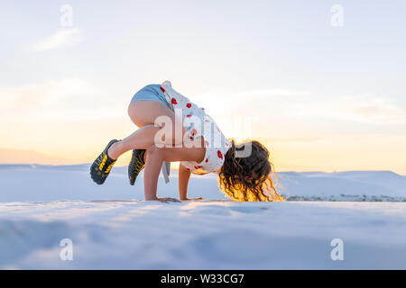Woman exercising doing crow exercise balancing on hands in white sands dunes national monument in New Mexico view of sunset - Stock Photo