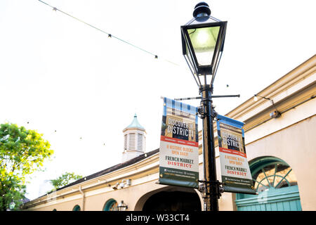 New Orleans, USA - April 22, 2018: French market district street sign on lamp post promoting historic blocks in French quarter in Louisiana famous cit - Stock Photo
