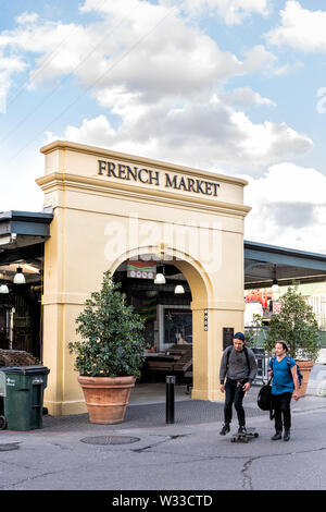 New Orleans, USA - April 22, 2018: French market sign and entrance in city quarter with many stores and restaurants and people walking on street in su - Stock Photo