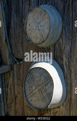 Two tin baths for both adults and kids hanging on a cottage wall. - Stock Photo