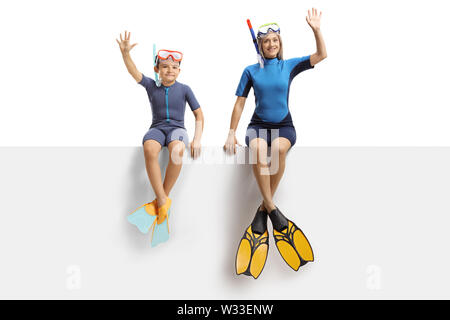 Full length portrait of a boy and a woman on a panel waving and wearing a wetsuit, a diving mask and diving flippers isolated on white background - Stock Photo