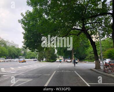 Beijing, China. 10th July, 2019. Photo taken with a mobile phone shows a woman riding a shared bike near Xuanwumen Subway Station in Beijing, capital of China, July 10, 2019. Credit: Wang Junlu/Xinhua/Alamy Live News - Stock Photo