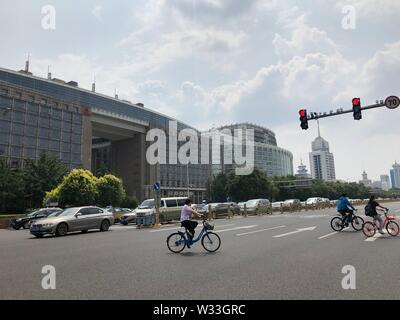 Beijing, China. 10th July, 2019. Photo taken with a mobile phone shows a woman riding a shared bike in Beijing, capital of China, July 10, 2019. Credit: Wang Junlu/Xinhua/Alamy Live News - Stock Photo