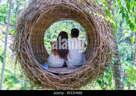 Asian woman and man enjoying his time sitting on a bird nest in the tropical jungle near the rice terraces in island Bali, Indonesia . Nature and trav