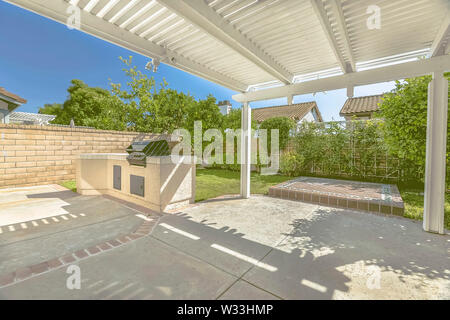 Concrete patio of a home with barbecue grill and white wooden pergola. Brick fence and lush greenerty surrounds the sunlit outdoor space. - Stock Photo