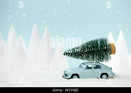 Retro car toy carrying Christmas fir tree in snowy landscape. Christmas or New Year celebration concept. Copy space. Selective focus - Stock Photo
