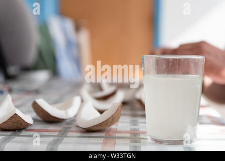 Coconut water and fresh pieces coconut on the table. Exotic food form Dominican Republic. - Stock Photo