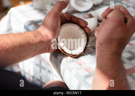 Man cut fresh coconut into pieces, process close up. Exotic food at home - Stock Photo