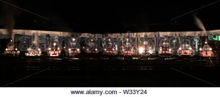 A lot of steam locomotives in front of the roundhouse during a night photo parade during the 50th anniversary of the bavarian railway museum - Stock Photo