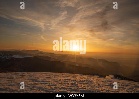 sunset with hills and colorful sky from Veterne hill on Martinske hole in winter Mala Fatra mountains in Slovakia - Stock Photo