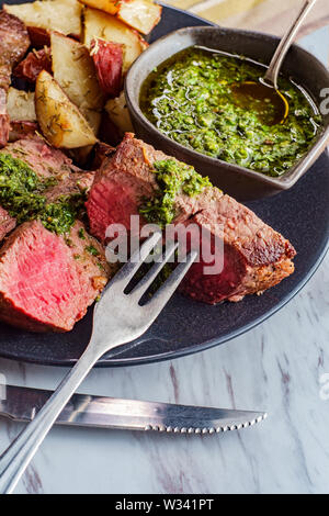 Juicy rare chimichurri verde grilled steak and red potatoes - Stock Photo