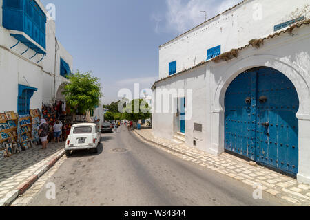 Sidi Bou Said, Tunisia - June.06, 2019: Alley with traditional white houses and blue doors. - Stock Photo
