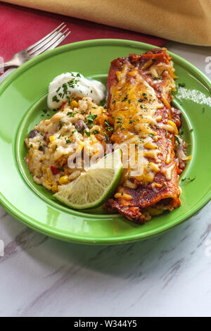 Authentic Mexican chimichanga enchilada with sour cream and rice garnished with lime wedge - Stock Photo