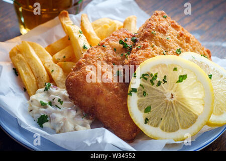 Authentic traditional British cuisine fish and chips served with an ice cold beer - Stock Photo