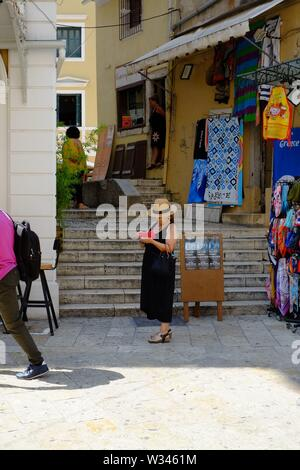 Corfu Corfu town A lady shopping is stood examining her mobile phone oblivious to what is going on around her. - Stock Photo