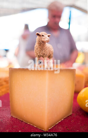 close up of organic spanish goat cheese piece with goat statuette on it and farmer in background in outdoor street food market on a sunny summer day - Stock Photo